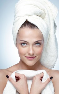 Closeup portrait of a happy woman with perfect skin and towel on head